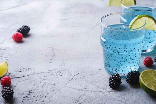 Saboroso coquetel de cor azul com sementes de chia de manjericão, fatia de limão cítrico, framboesa e amoras silvestres em dois copos