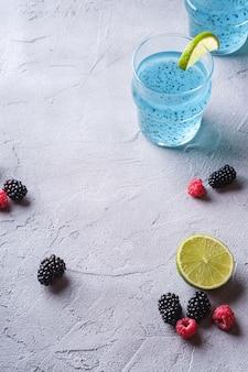 Saboroso coquetel de cor azul com sementes de chia de manjericão, fatia de limão cítrico, framboesa e amoras