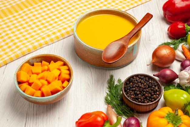 Saboroso creme de sopa de abóbora com textura de frente e legumes em uma mesa branca com molho de prato de sopa maduro