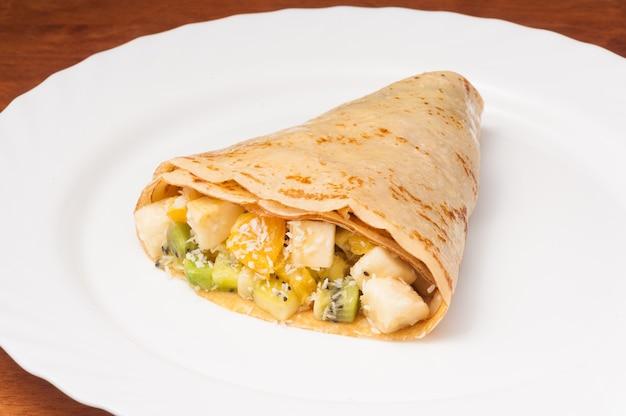 Saboroso crepe com banana, laranja e kiwi em prato branco