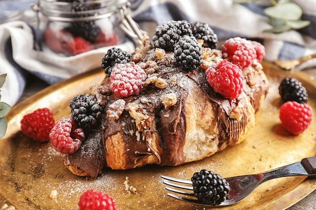Saboroso croissant com pasta de chocolate, nozes e frutas vermelhas na bandeja de metal