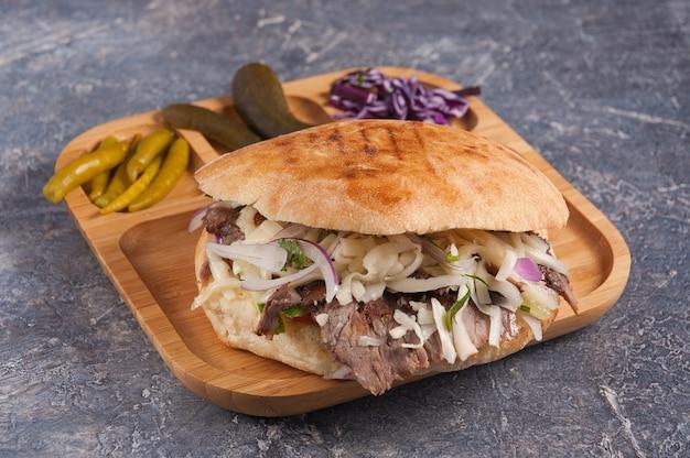 Saboroso doner turco com queijo de frango e cebola em um prato de madeira