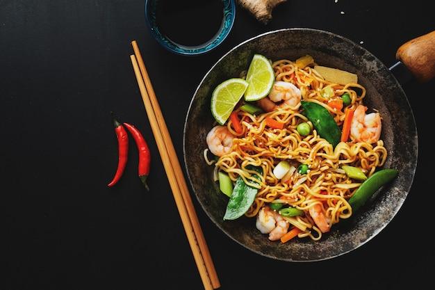 Saboroso e apetitoso macarrão asiático com legumes e camarões na frigideira em superfície escura