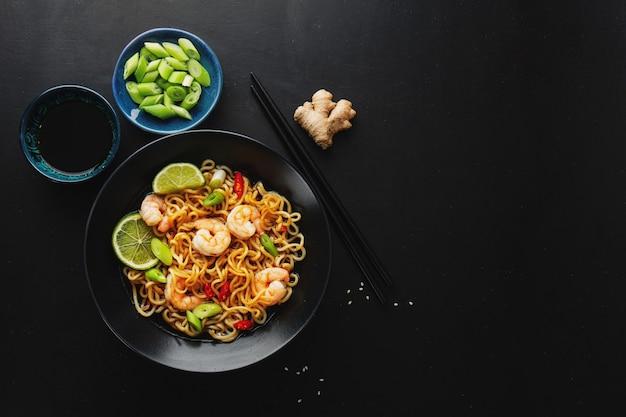 Saboroso e apetitoso macarrão asiático com legumes e camarões no prato em superfície escura