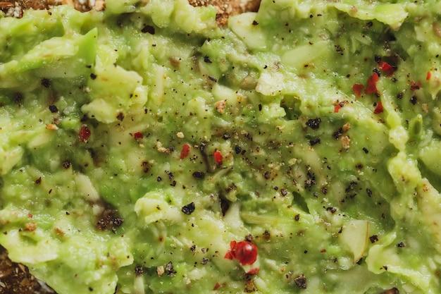 Saboroso e apetitoso pão crocante com purê de abacate servido no prato. fechar-se.