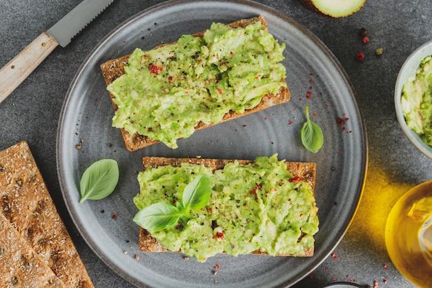 Saboroso e apetitoso pão crocante com purê de abacate servido no prato.