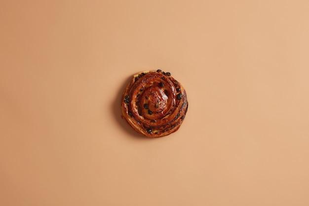 Saboroso e apetitoso puff redondo de pão macio em espiral com passas assadas na padaria. produto de panificação com alto teor calórico, contendo muita gordura e açúcar. rolo caseiro no fundo bege do estúdio. conceito de comida doce.