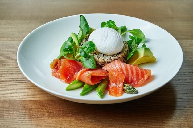 Saboroso e saudável café da manhã continental - quinoa com ovos de benedict, espinafre, abacate, salmão salgado e aspargos em tigela branca. mesa de madeira