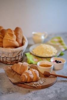 Saboroso e saudável café da manhã, queijo cottage natural, croissant fresco com mel. manhã ainda vida. produtos de confeitaria.