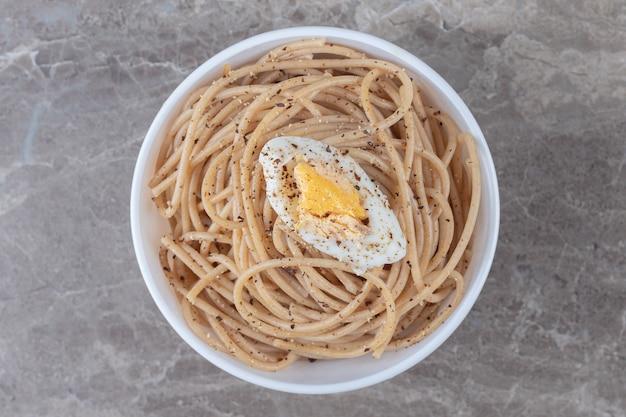 Saboroso espaguete com ovo em uma tigela branca.