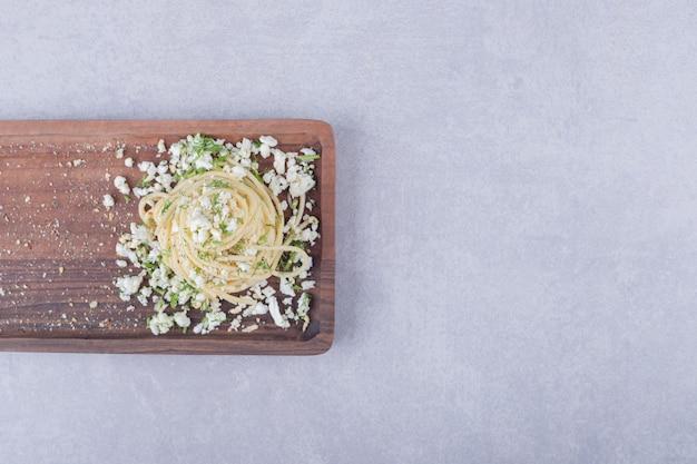 Saboroso espaguete cozido com queijo ralado na placa de madeira.