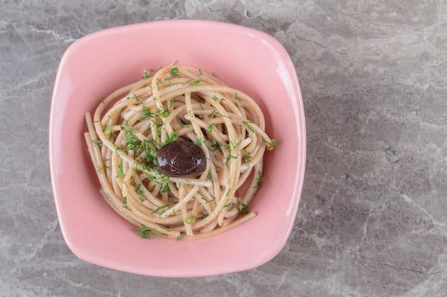 Saboroso espaguete decorado com verdes em uma tigela rosa.