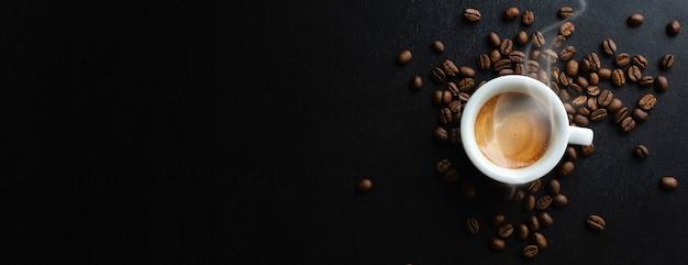 Saboroso espresso fumegante na xícara com grãos de café. vista de cima. fundo escuro.
