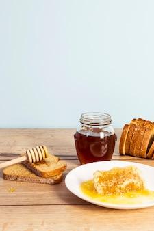 Saboroso favo de mel orgânico e fatia de pão para pequeno-almoço saudável