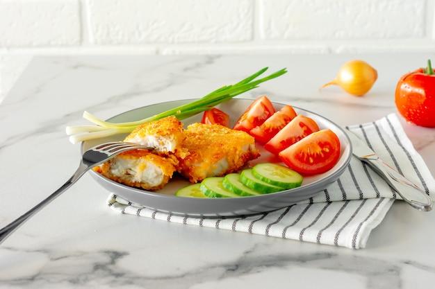 Saboroso filé de peixe assado na farinha de rosca e legumes frescos em um prato. jantar saudável.