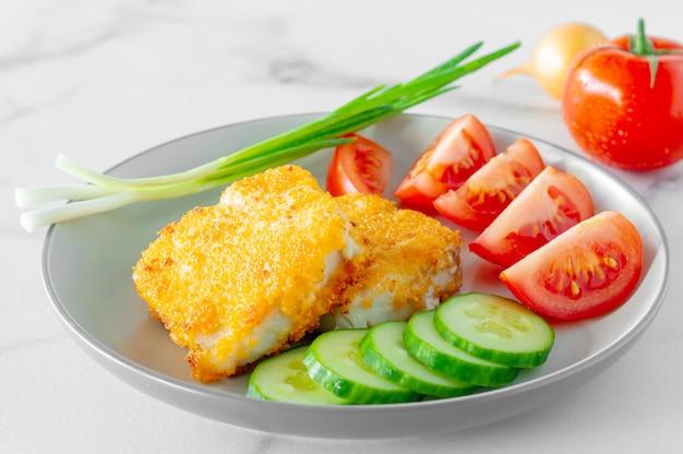Saboroso filé de peixe assado na farinha de rosca e legumes frescos em um prato. jantar saudável. Foto Premium