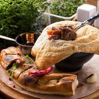 Saboroso goulash de carne com legumes sob a massa folhada. fechar-se