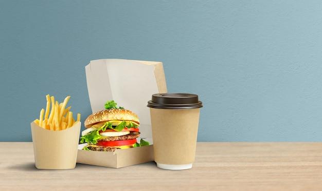 Saboroso hambúrguer, batata frita e café em embalagem de papelão para viagem.