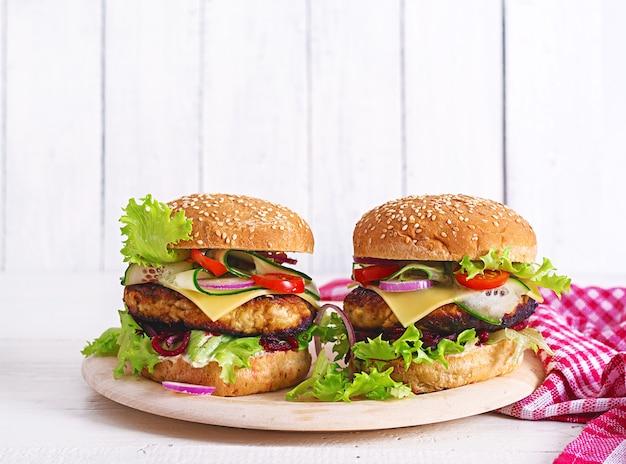 Saboroso hambúrguer caseiro grelhado com frango hambúrguer, tomate, queijo, pepino, alface e beterraba. sanduíche. almoço