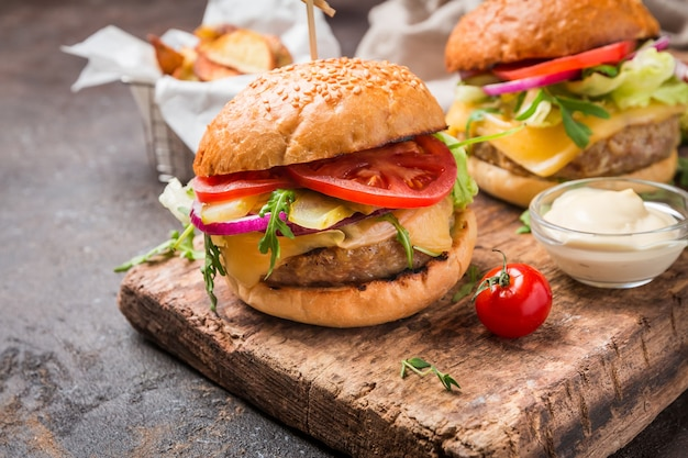 Saboroso hambúrguer clássico de carne grelhada com molho de alface e maionese em mesa de madeira rústica com espaço de cópia