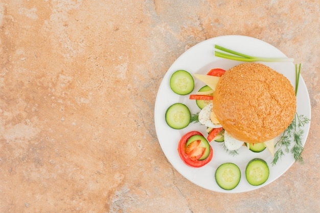 Saboroso hambúrguer com rodelas de pepino e tomate