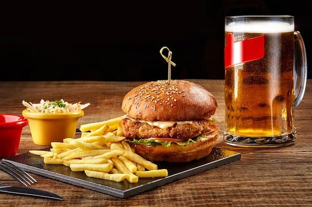 Saboroso hambúrguer de batata frita com molho e copo de cerveja no quadro negro