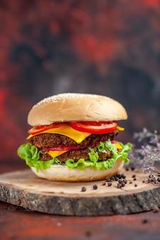 Saboroso hambúrguer de carne com queijo e salada de frente no chão escuro
