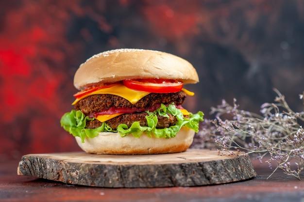 Saboroso hambúrguer de carne com queijo e salada de frente no fundo escuro