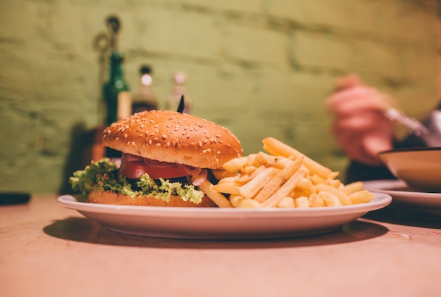 Saboroso hambúrguer delicioso no prato no café. batatas fritas ao lado com hambúrguer suculento.