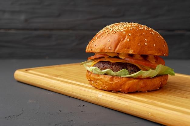 Saboroso hambúrguer em madeira preta close up