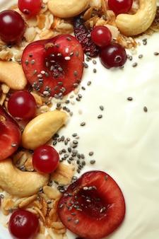 Saboroso iogurte com diferentes ingredientes, close-up