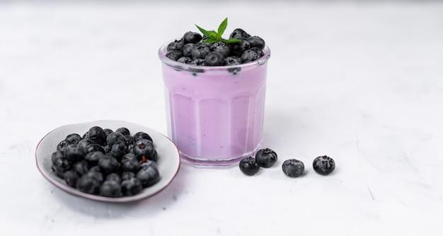 Saboroso iogurte de mirtilo fresco agitar sobremesa em pé de vidro no fundo da mesa branca. batido caseiro de baga. alimentação saudável. iogurte alimentar diet