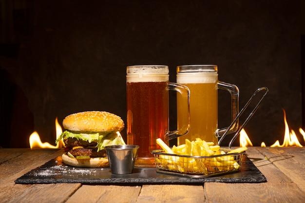 Saboroso jantar com dois copos de cerveja, hambúrguer e batatas fritas.