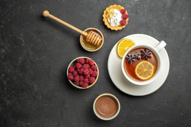 Saboroso jantar com uma xícara de chá preto com limão, chocolate e biscoitos de mel de framboesa em fundo escuro