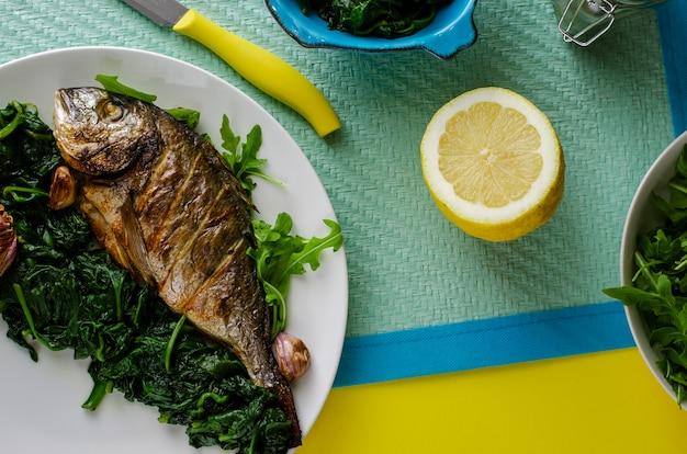 Saboroso jantar italiano ou almoço com peixe dorada assado ou dourada, guarnecido com espinafre em fundo azul