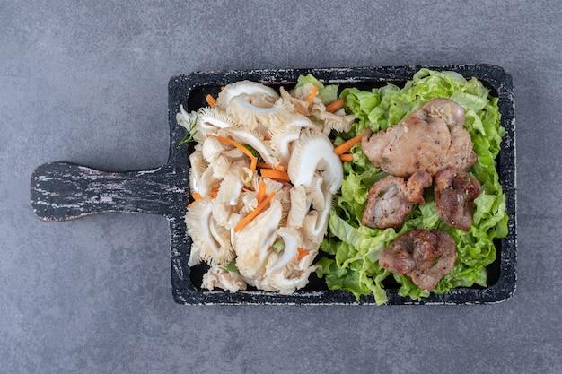 Saboroso kebab grelhado e salada de legumes na placa de madeira.