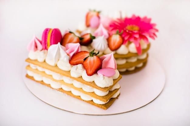 Saboroso lindo bolo rosa com macaroons de marshmallows de morangos e uma flor enorme
