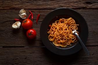 Saboroso macarrão espaguete clássico apetitoso com tomate pimenta no prato na mesa escura
