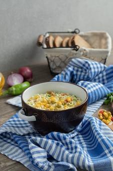 Saboroso macarrão na tigela e cesta de pão na mesa de madeira