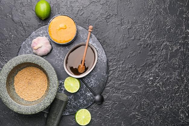 Saboroso molho de mostarda e mel com ingredientes na mesa escura