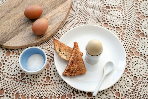 Saboroso ovo cozido em uma xícara com pão torrado crocante no café da manhã. refeição saudável na mesa da cozinha.