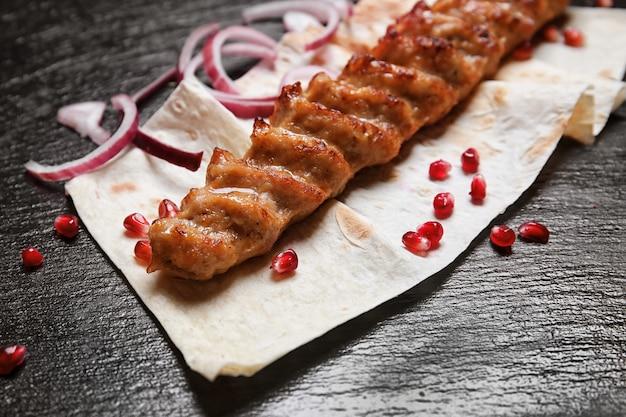Saboroso pão achatado com kebab de lulah na mesa escura