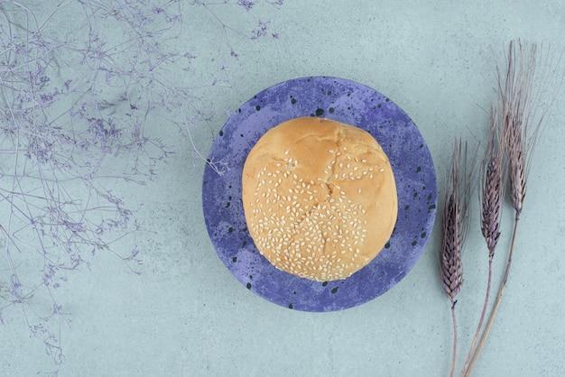 Saboroso pão de hambúrguer com sementes de gergelim em prato azul