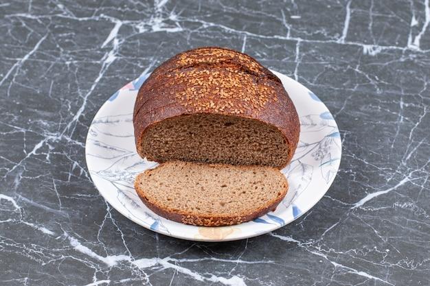Saboroso pão preto com gergelim no prato, na superfície de mármore