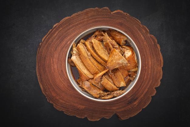 Saboroso pato cozido chinês marrom em uma tigela com madeira natural
