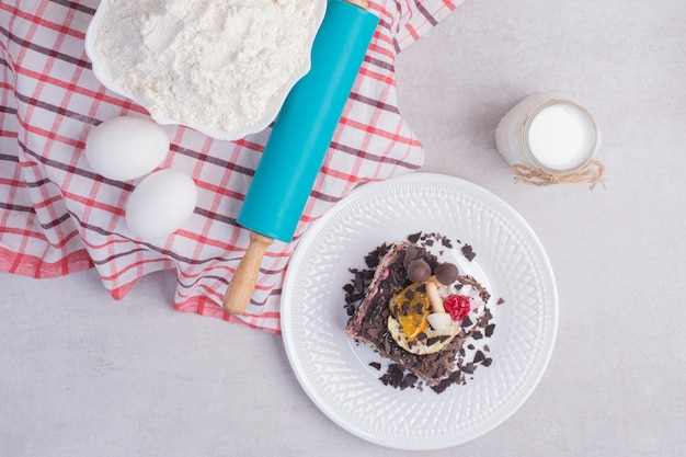 Saboroso pedaço de bolo com ovos, leite e farinha na mesa branca.
