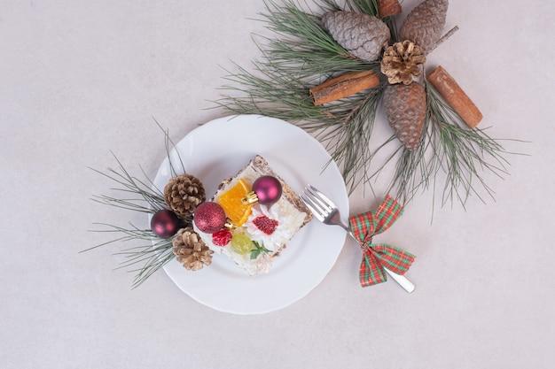 Saboroso pedaço de bolo com pinhas e galho de árvore