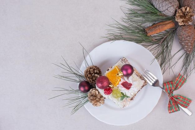 Saboroso pedaço de bolo com pinhas e galho de árvore.