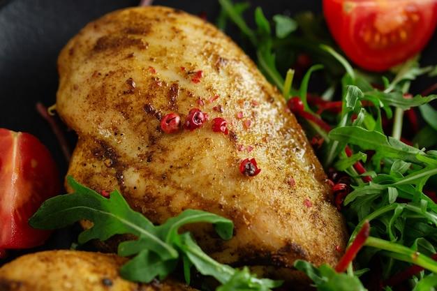 Saboroso peito de frango grelhado com legumes e salada servida na mesa escura. fechar-se.