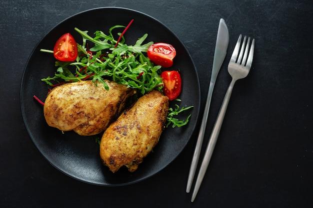 Saboroso peito de frango grelhado com legumes e salada servida na mesa escura.